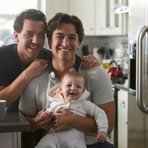 Male gay couple with baby girl in kitchen looking
